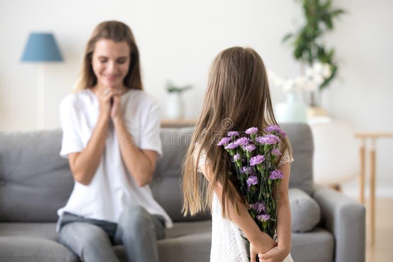 De bloemen die van de dochterholding mamma met moedersdag gelukwensen, aangaande stock foto