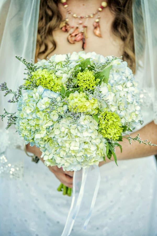 De bloemen van de bruidholding stock foto