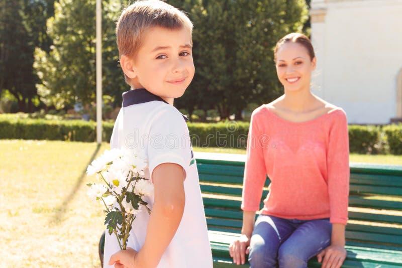 De bloemen van de jongensholding achter zijn rug royalty-vrije stock foto