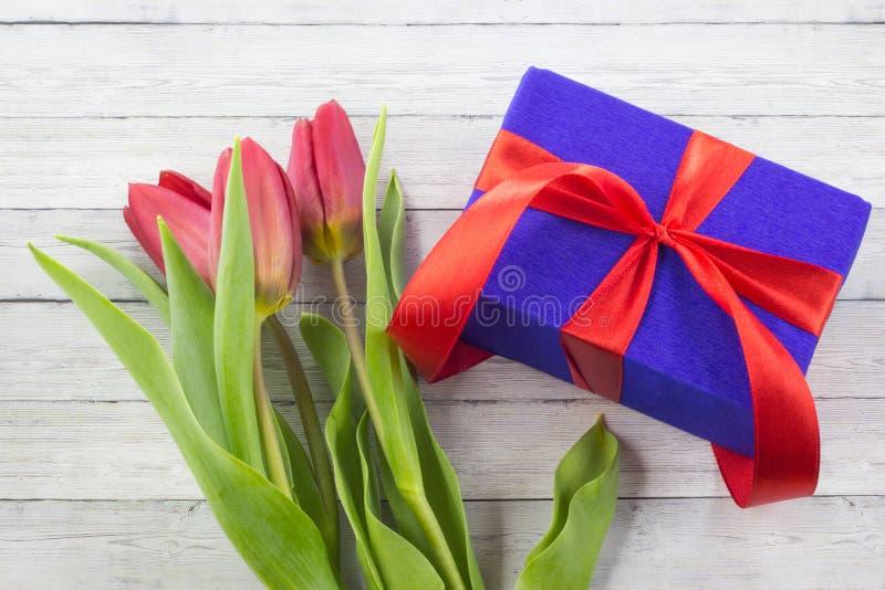 De bloemen van de de lentetulp, giftvakje op houten lijst royalty-vrije stock foto