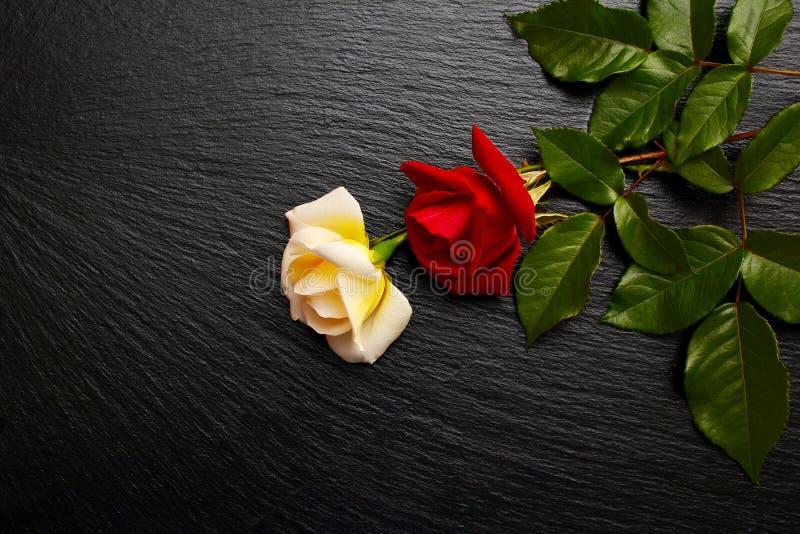 De bloemen van rode en witte rozen op zwarte lei schepen in, plateren, tra royalty-vrije stock foto's