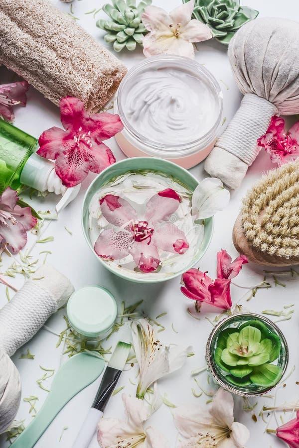 De bloemen in water werpen en diverse van de van het schoonheidswellness, kuuroord en massage toebehoren plaatsend op witte achte stock fotografie