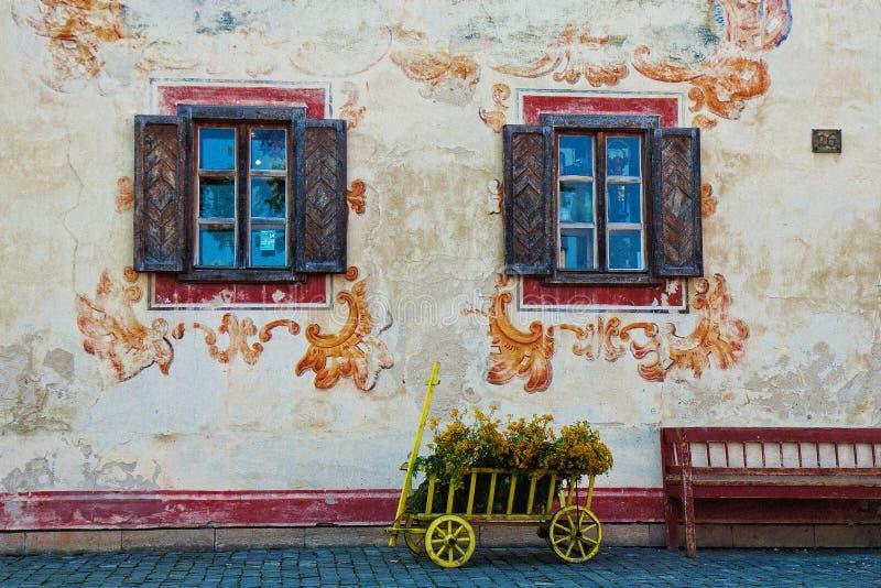 De bloemenkar op wielen met bloemen wordt gevestigd tussen twee vensters Geen mensen in de straat in Lublin, Polen, stock afbeeldingen