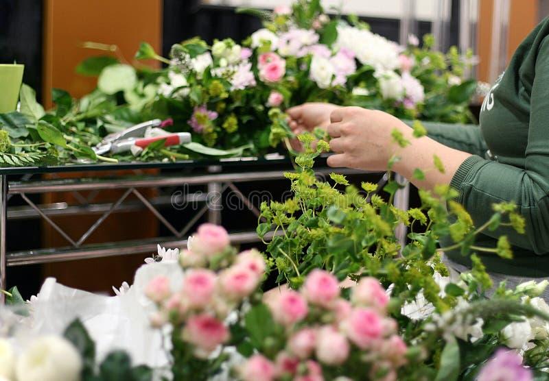 De bloemist die samenstelling van bloemen creëren stock foto