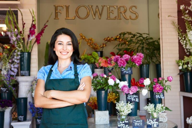De bloemist die van de vrouw zich buiten winkel bevindt stock afbeeldingen