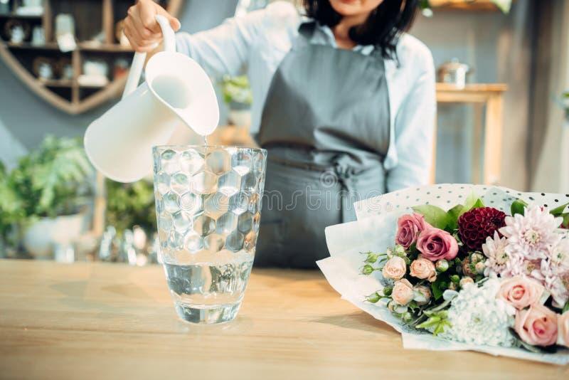 De bloemist giet water in een vaas in bloemwinkel stock fotografie