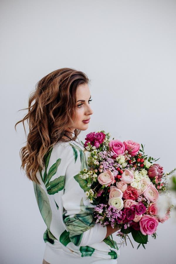 De bloemist maakt een boeket in een lichte studio royalty-vrije stock fotografie