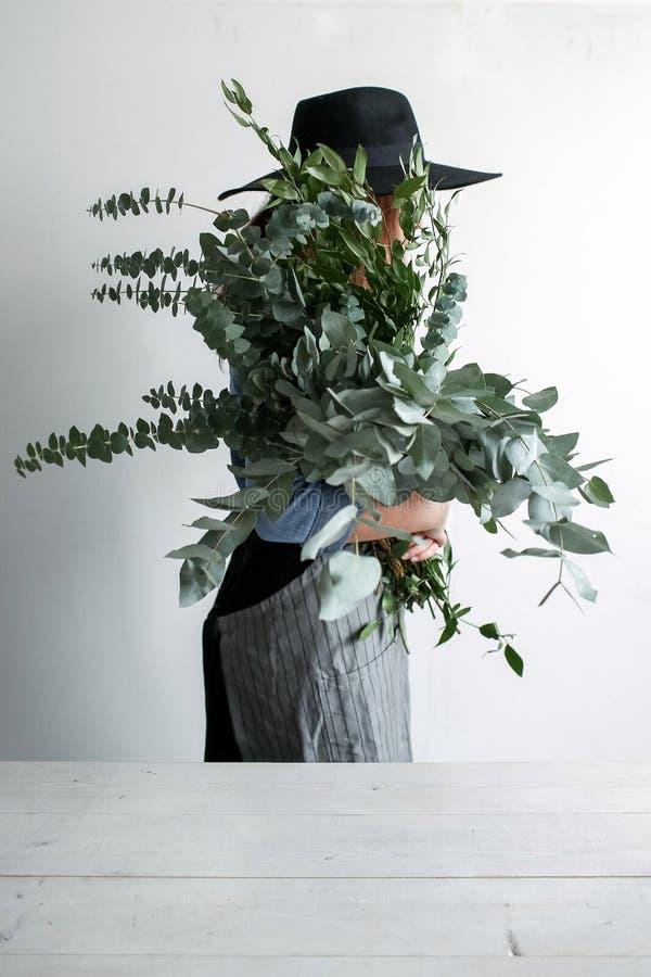 De bloemist maakt een boeket Proces van het werk vrouw die een boeket van eucalyptus in handen houden stock afbeeldingen