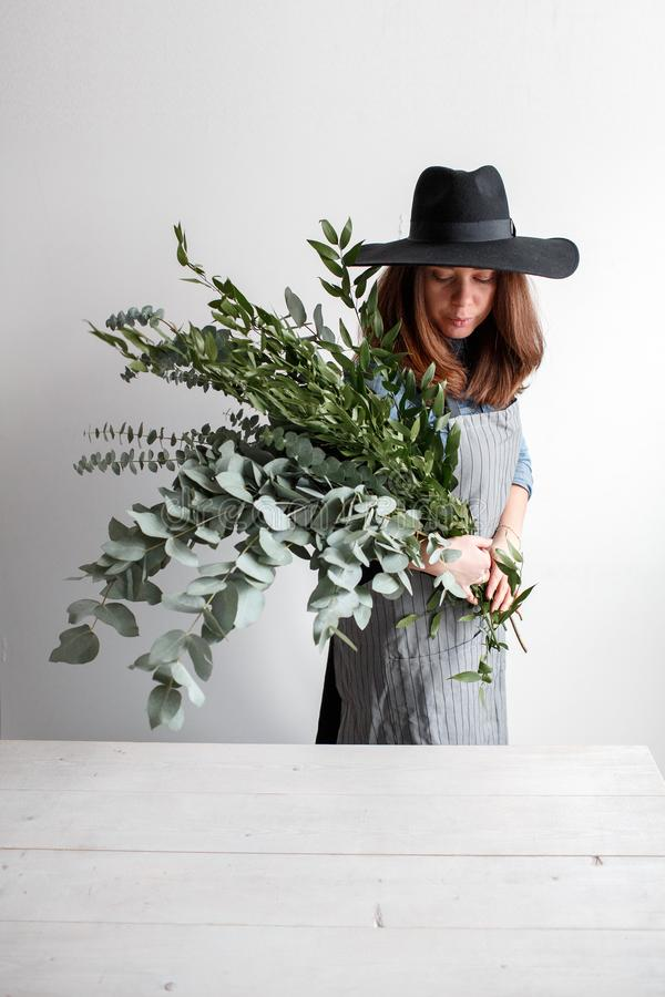 De bloemist maakt een boeket Proces van het werk vrouw die een boeket van eucalyptus in handen houden stock fotografie