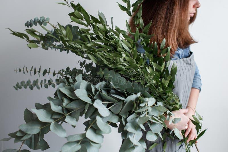 De bloemist maakt een boeket Proces van het werk vrouw die een boeket van eucalyptus in handen houden royalty-vrije stock afbeelding
