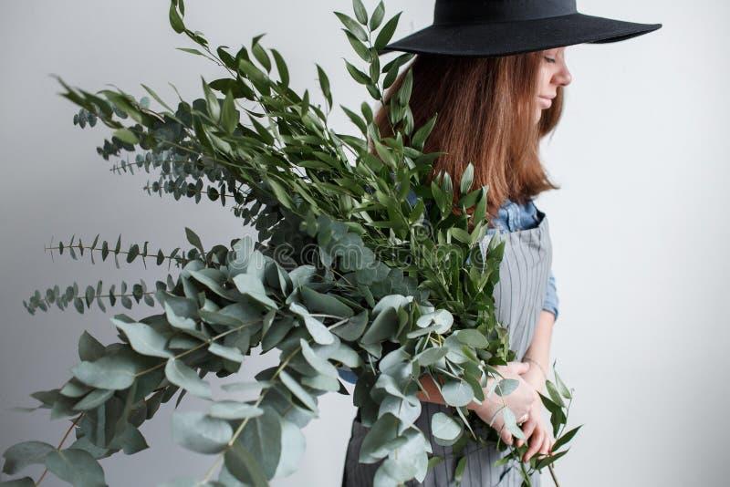 De bloemist maakt een boeket Proces van het werk vrouw die een boeket van eucalyptus in handen houden royalty-vrije stock afbeeldingen