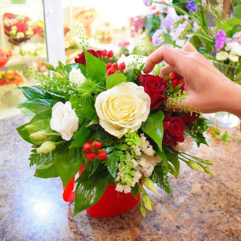 De bloemist maakt samenstelling van bloemen in doos royalty-vrije stock afbeelding