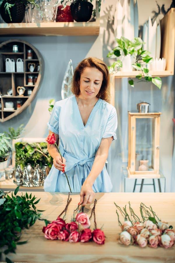 De bloemist sorteert rozen op de lijst in bloemwinkel royalty-vrije stock afbeelding
