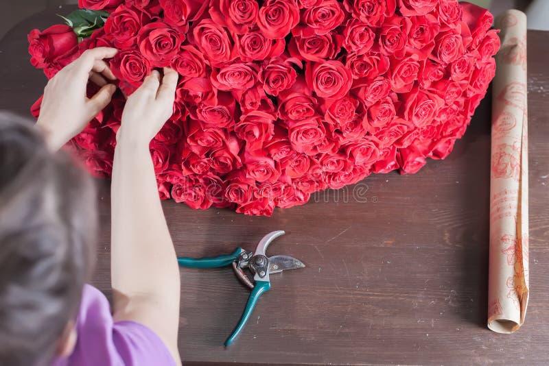 De bloemistvrouw bereidt een groot boeket van rode rozen voor stock afbeelding