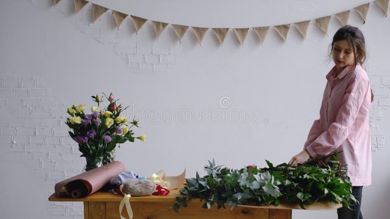 De bloemistwerken in de werkplaats stock fotografie
