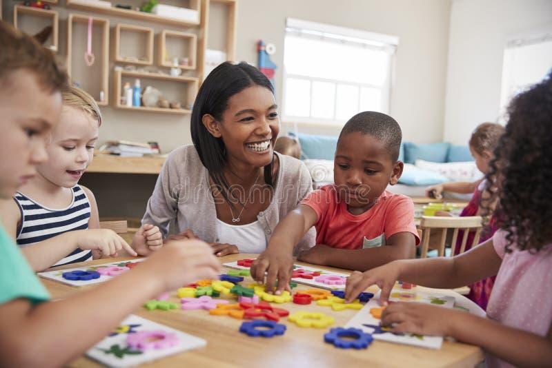 De Bloemvormen van leraarsand pupils using in Montessori-School royalty-vrije stock afbeeldingen