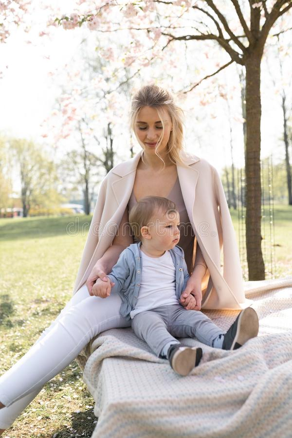 De bloesem van de Sakurakers - de jonge zitting van de mammamoeder met haar weinig zoon van de jongensbaby in een park in Riga, L stock afbeeldingen