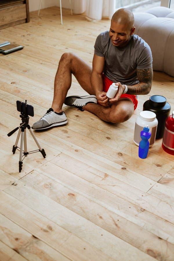 De blog van de sportmanfilm op smartphone terwijl het zitten op de vloer royalty-vrije stock foto