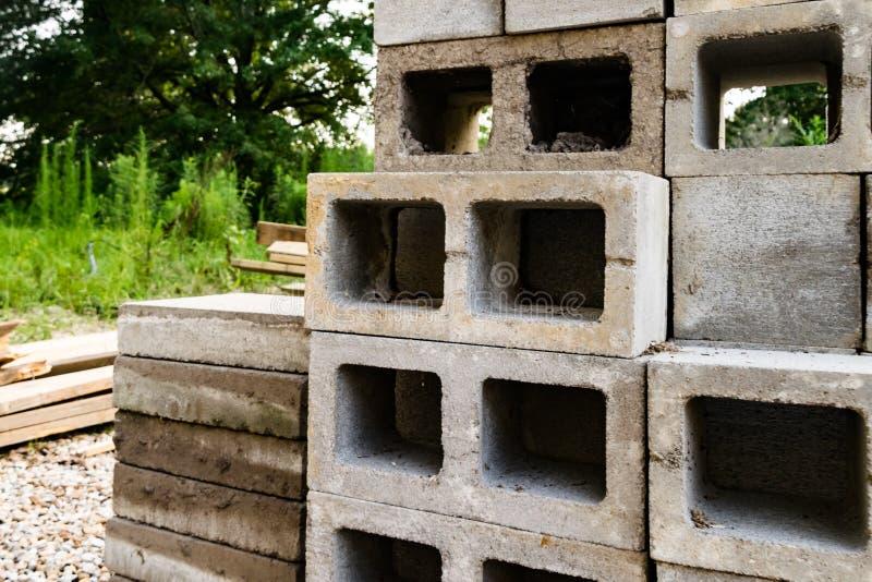 De blokken en het timmerhout van de huisbouw site=Concrete stock foto's