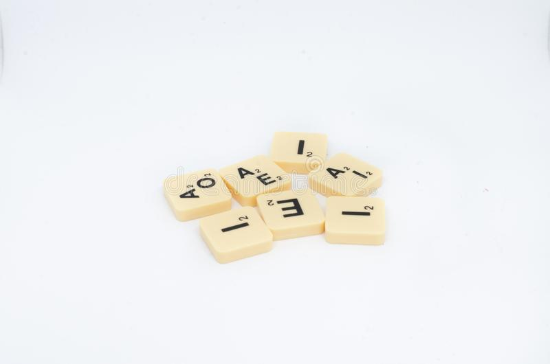 De blokken van de het spelbrief van de scrabbleraad op een witte achtergrond worden geïsoleerd die stock afbeelding
