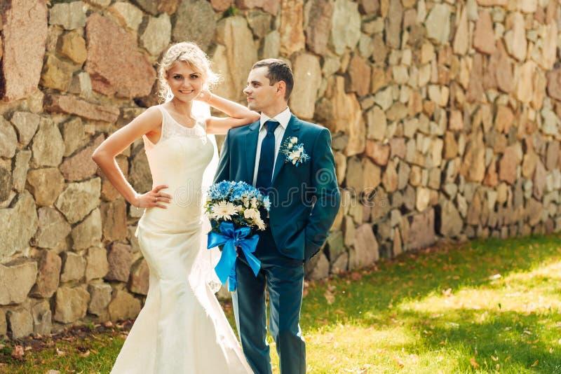 De blonde bruid en haar bruidegom bevinden zich op het gras in een exotisch park royalty-vrije stock afbeelding