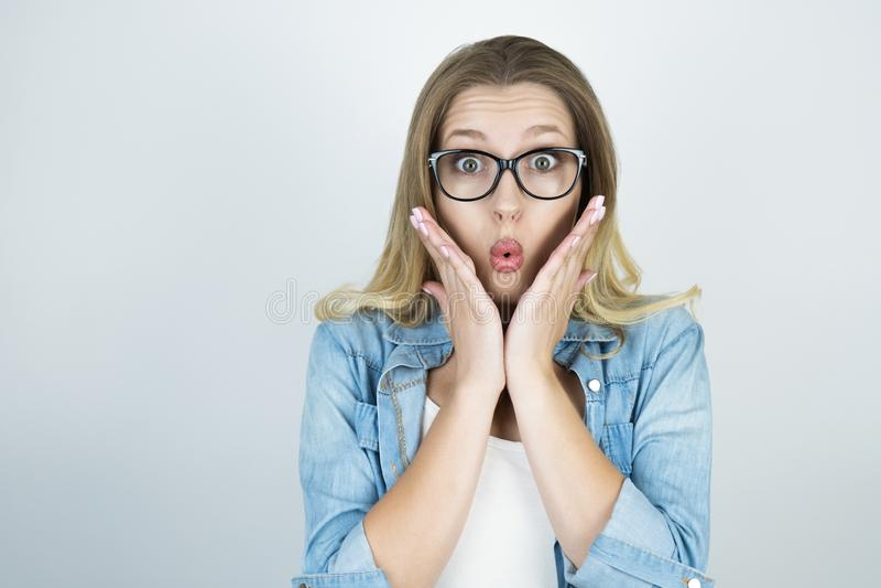 De blonde die handen van de meisjesholding dichtbij gezicht worden verrast isoleerden witte achtergrond stock foto's