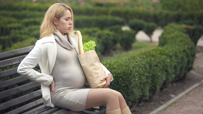 De blonde het denken zak van de de holdingskruidenierswinkel van de dame rustende bank, zwangerschapsmoeilijkheden stock afbeelding