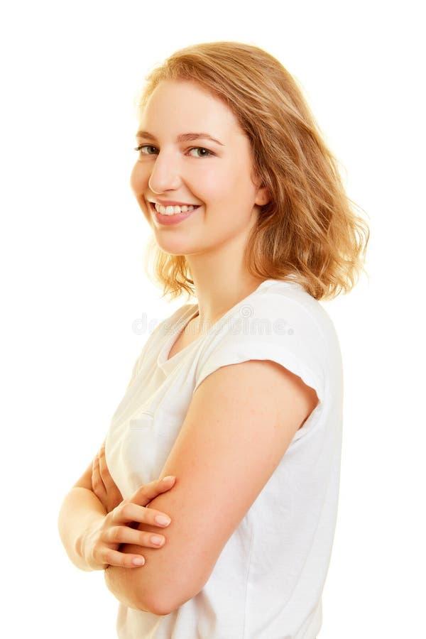 De blonde jonge vrouw glimlacht met gekruiste wapens royalty-vrije stock fotografie