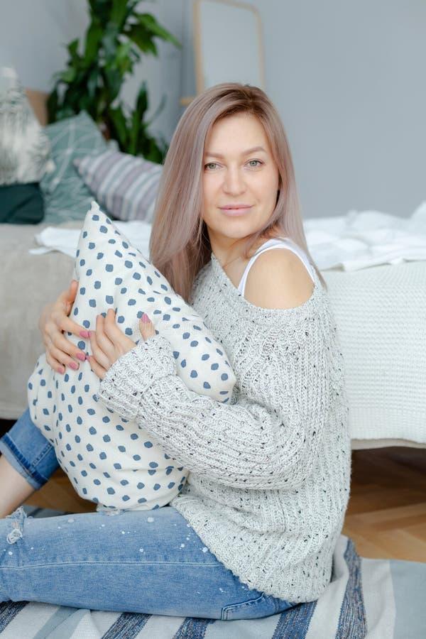 Is de blonde jonge vrouw in grijze trui dichtbij bed stock afbeeldingen