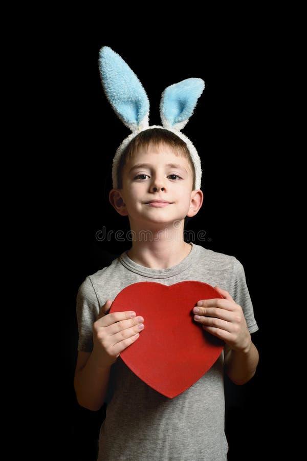 De blonde jongen in hazenoren houdt de rode doos van de hartvorm op zwarte achtergrond Liefde en Familieconcept Verticaal kader royalty-vrije stock fotografie