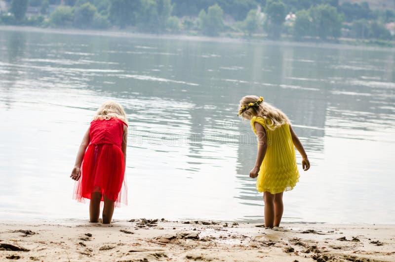 De Blonde Meisjes In Rode Kleding En Gele Kleding Bij De Rivier Lopen Vast Stock Foto