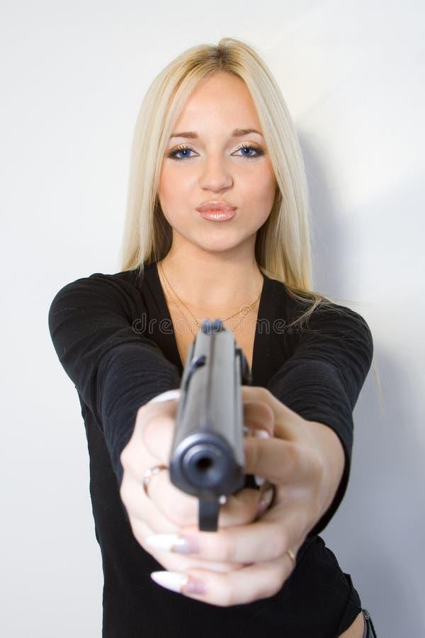 De blonde met een pistool stock afbeelding