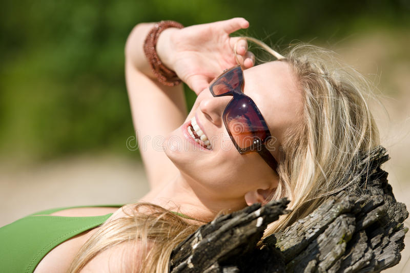 De blonde vrouw in bikini zonnebaadt op strand stock fotografie