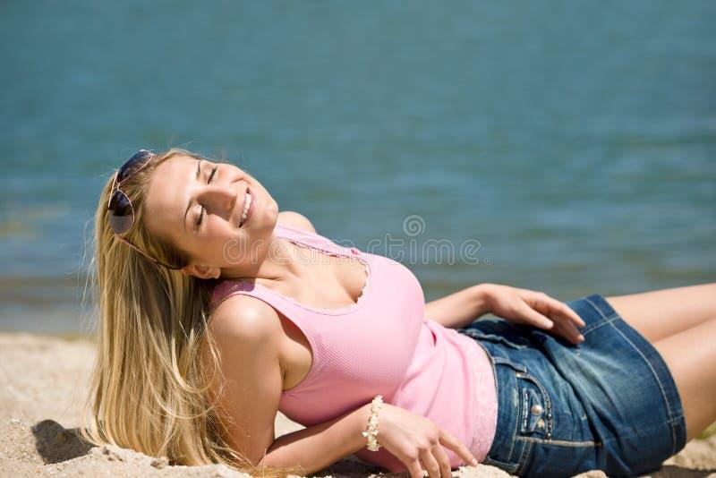De blonde vrouw geniet de zomer van zon op strand royalty-vrije stock foto's