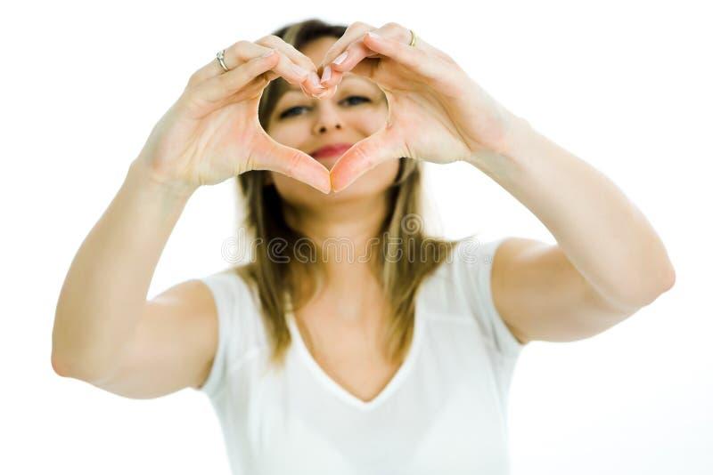 De blonde vrouw toont hartvorm met handen - kijkend door het hart stock afbeelding