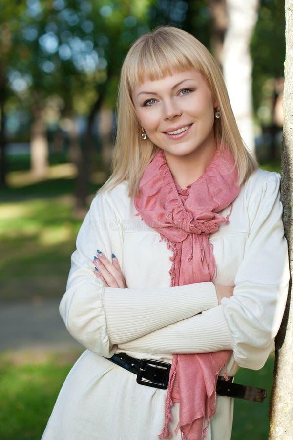 De blonde vrouw van Smilng dichtbij boom royalty-vrije stock fotografie