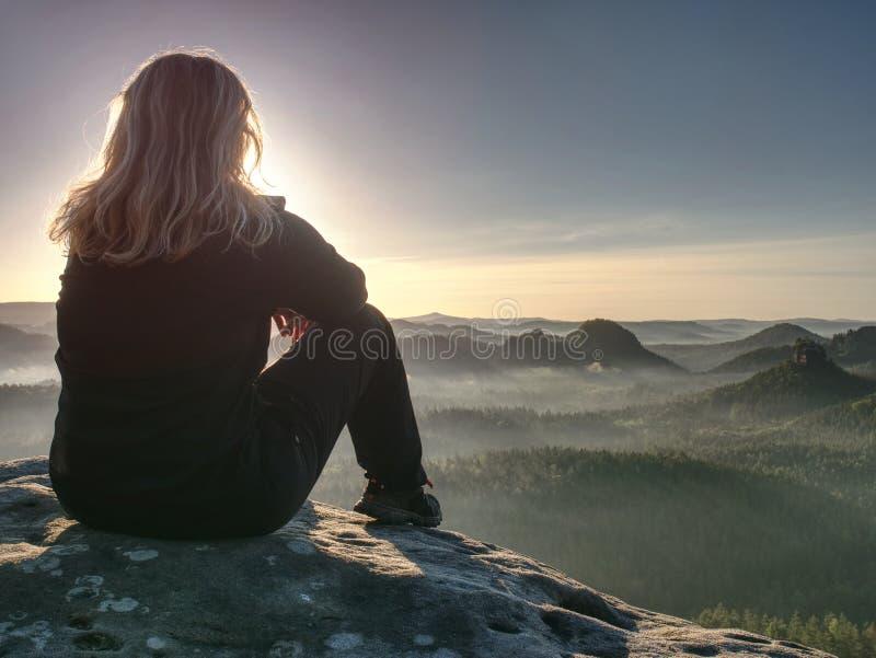 De blonde vrouwenzitting op rand van de bergklip tegen surise stock afbeeldingen