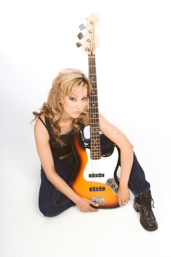De blonde zitting van de de vrouwengitarist van Latina op vloer royalty-vrije stock foto