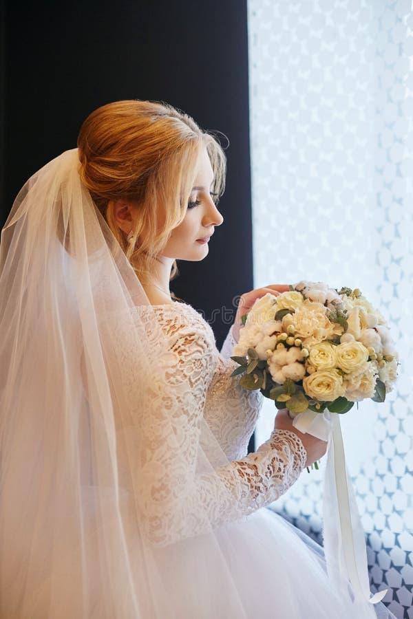 De blondebruid in een witte huwelijkskleding en een lange sluier wacht stock afbeelding