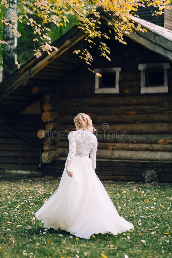 De blondebruid loopt in fladderende kleding op blokhuisachtergrond Achter mening kunstwerk royalty-vrije stock foto's