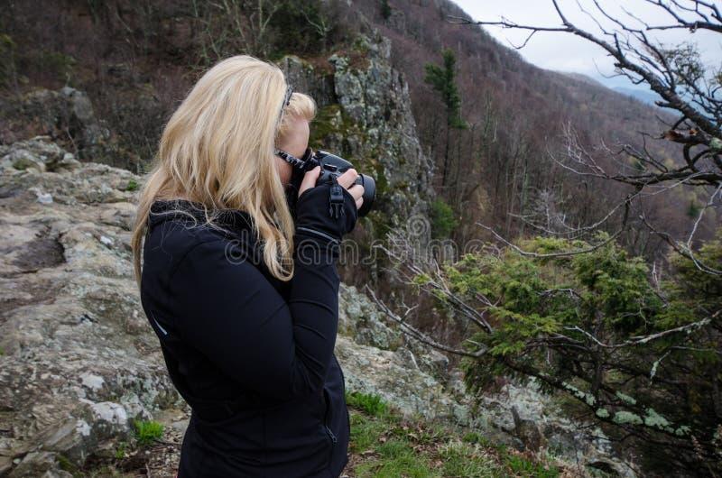 De blondefotograaf neemt foto's met een DSLR-camera van aard binnen van het Nationale Park van Shenandoah op een donkere dag stock foto's