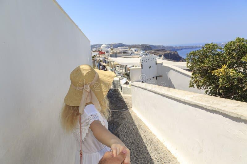 De blondeholding dient de straten van Fira in Santorini-eiland in stock fotografie