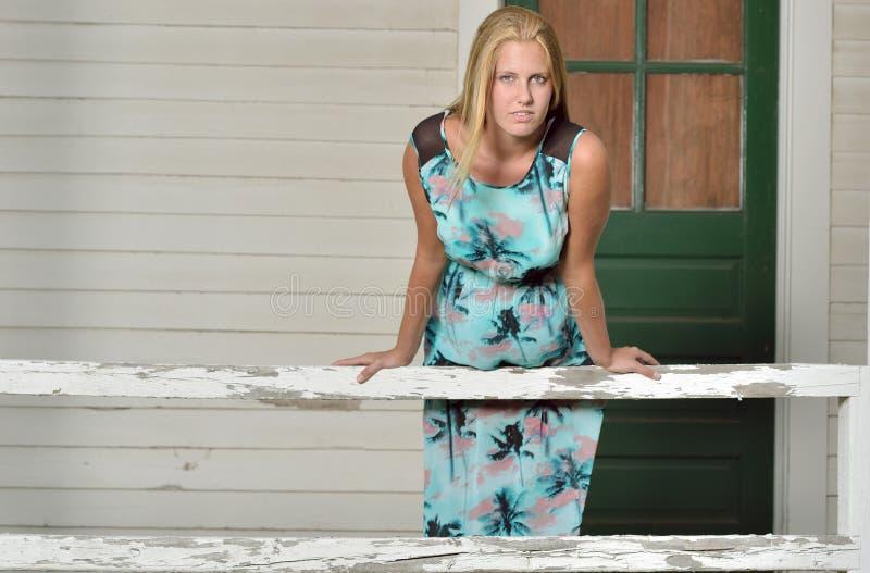 De blondemannequin stelt shuttered dichtbij huis stock afbeeldingen