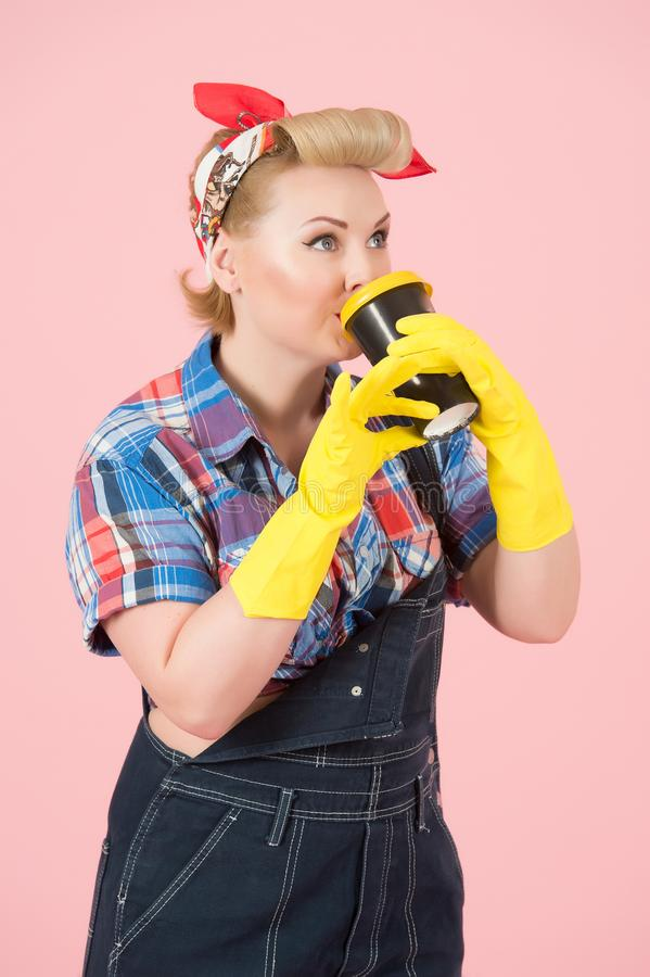 De blondemeisjes met gele handschoenen houdt en drinkt van kop met gele dekking De gelukkige speld-Omhooggaande gestileerde vrouw royalty-vrije stock fotografie