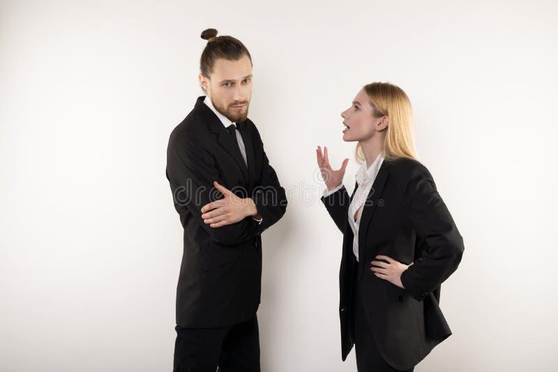 De blondeonderneemster verklaart aan haar partner haar standpunt geen dat hij wil goedkeuren stock foto
