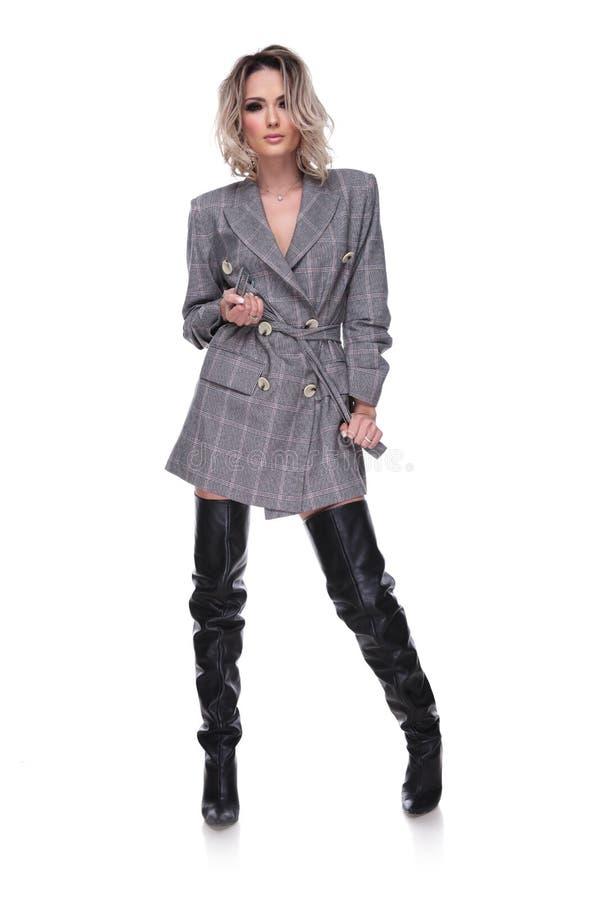 De blondevrouw bindt haar geruite grijze kostuum` s riem rond taille royalty-vrije stock afbeelding