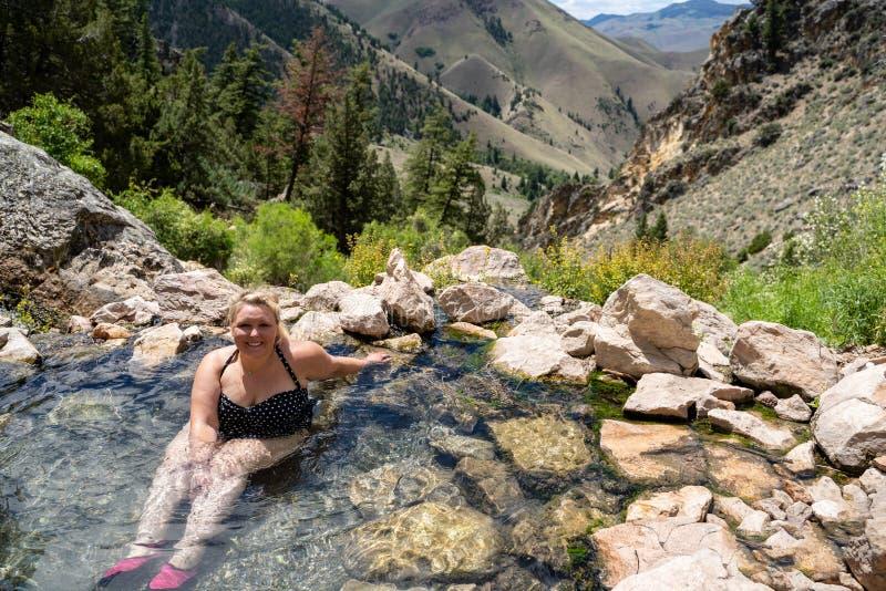 De blondevrouw die een stip dragen swimsut doorweekt en geniet van de Hete Lentes van Goldbug in Salmon Challis National Forest v royalty-vrije stock foto's