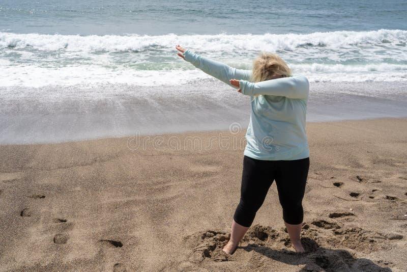 De blondevrouw doet een bettende dansbeweging op het strand stock afbeelding