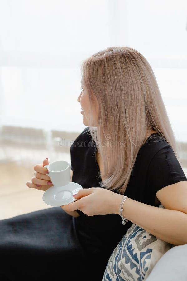 De blondevrouw in een zwarte kleding drinkt koffie royalty-vrije stock foto