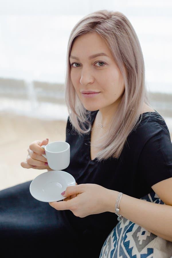 De blondevrouw in een zwarte kleding drinkt koffie stock afbeelding